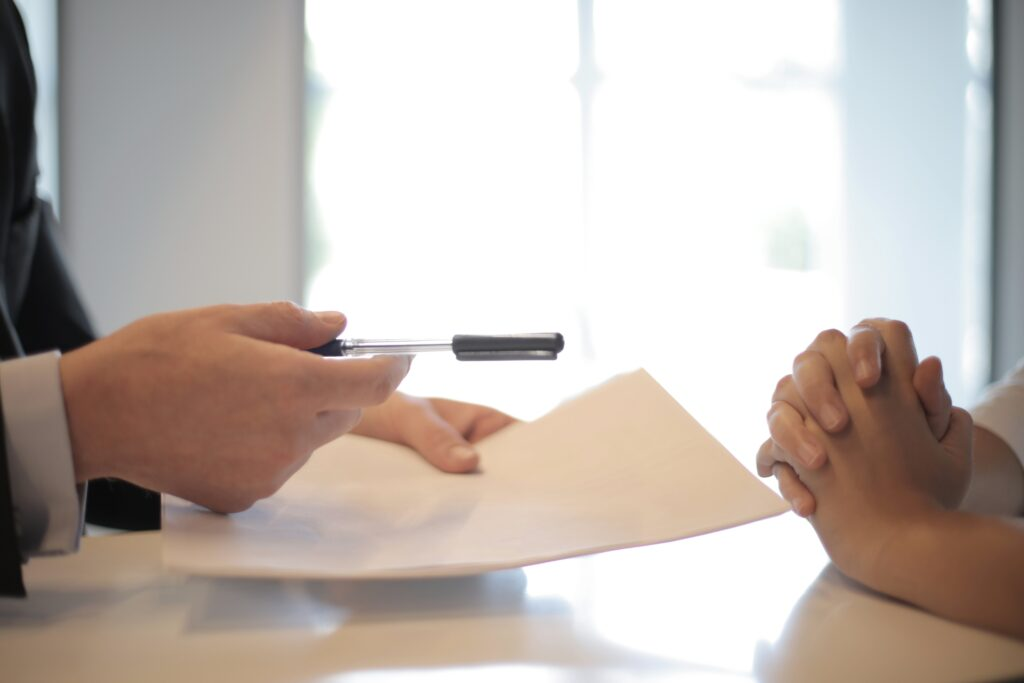 Man handing a pen and paper to a woman