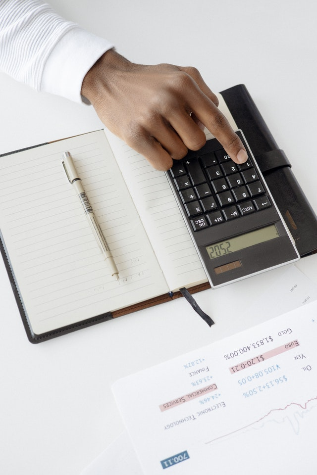 Calculator and notebook spread out on a desk