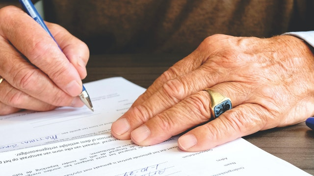 Man signing a document with a pen