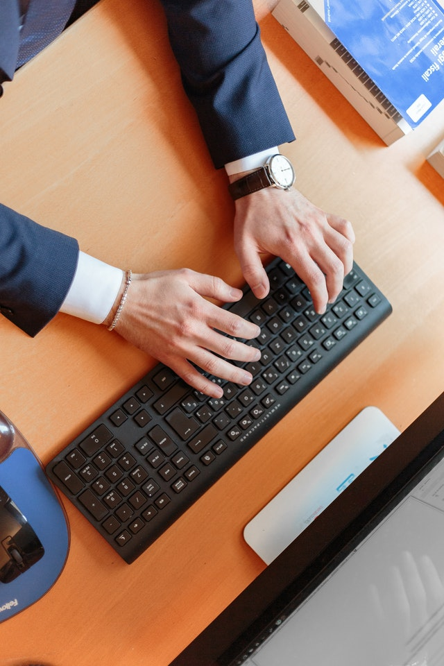 Man in suit typing on a keyboard