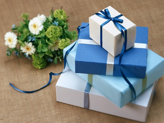 Picture of Blue Presents Next to Flowers