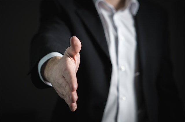 Man in suit with hand out for a handshake