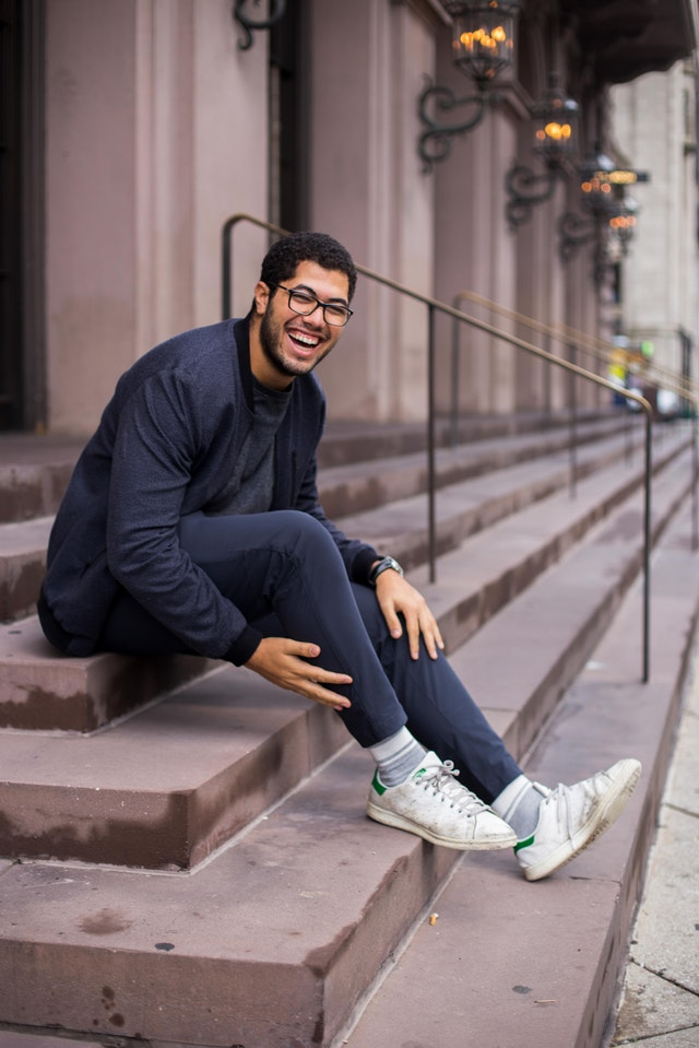 Smiling man sitting on stone steps
