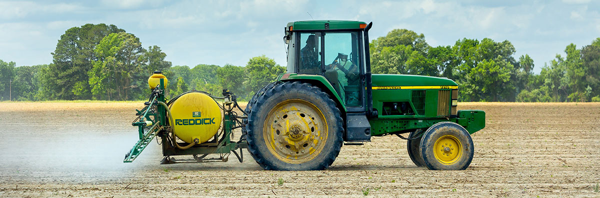 Green tractor spraying a field