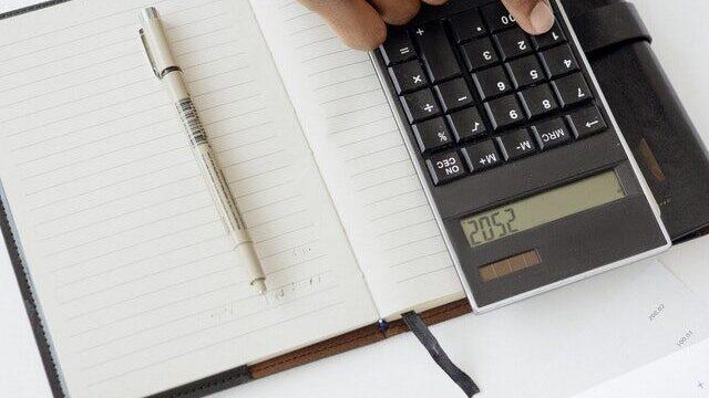 Man using a calculator next to a notebook on a desk