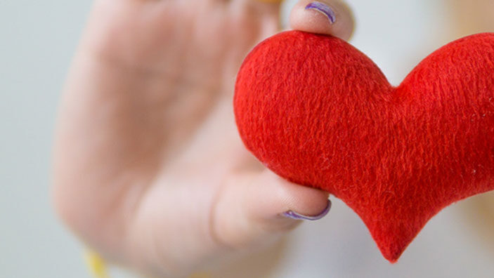 Hand holding crafted red heart