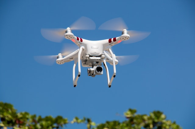 Pictures of a White and Red Drone Flying against a blue sky.
